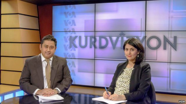 "A man and a woman sit in front of a big screen displaying ""Kurdvizyon."""