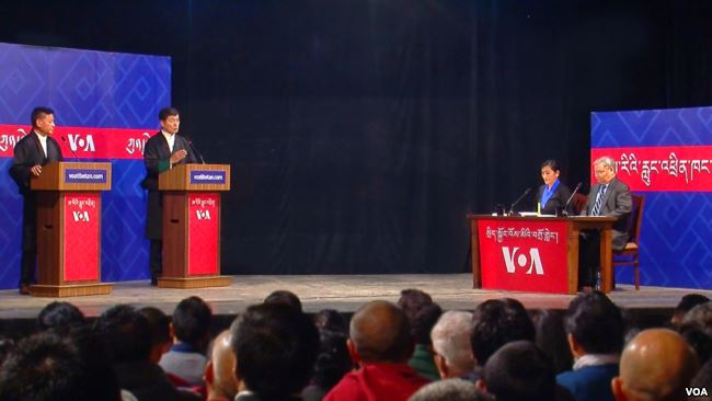 Two men stand behind podiums on the left, and a man and a woman sit at a table on the right.