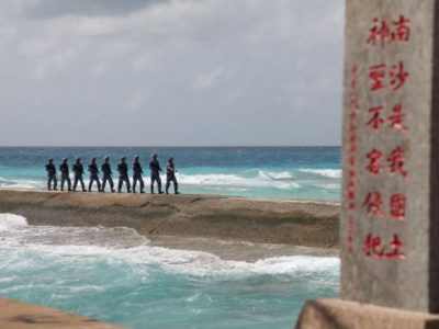 Troops march in a line on a sand bank near the ocean