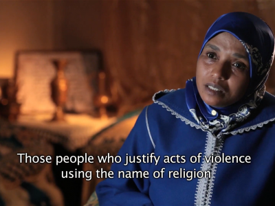 "A woman, wearing a headscarf, says ""those people who justify acts of violence using the name of religion"""